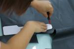 Ein Teil einer Handtasche wird mit Hilfe einer Schablone ausgeschnitten